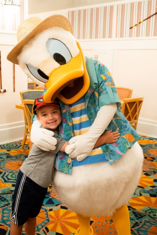 Boy hugging Donald Duck in a blue outfit