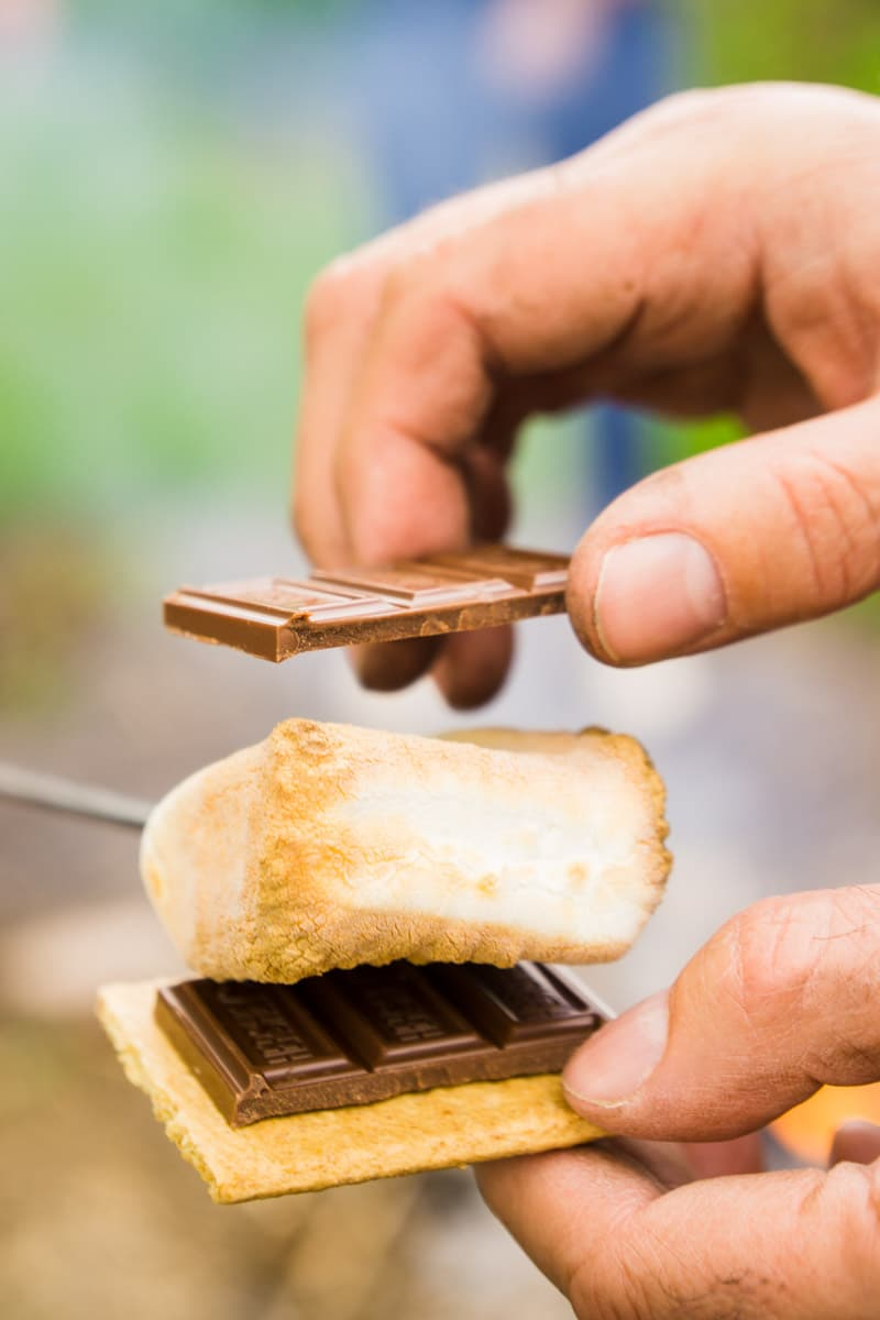 Putting a s'more together from a DIY s'more bar