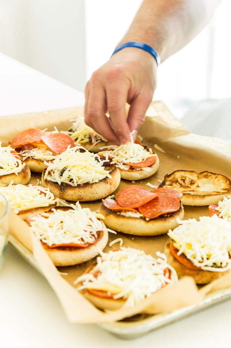 Adding toppings to English muffin pizzas