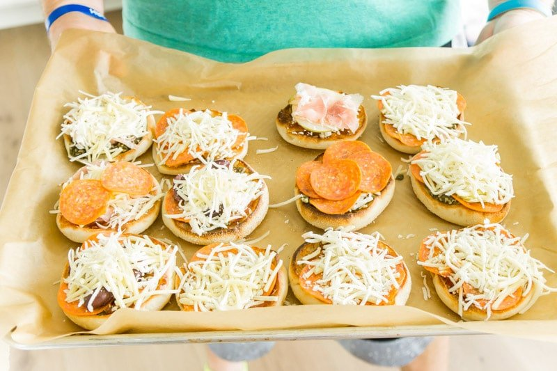 A tray filled with finished English muffin pizza options