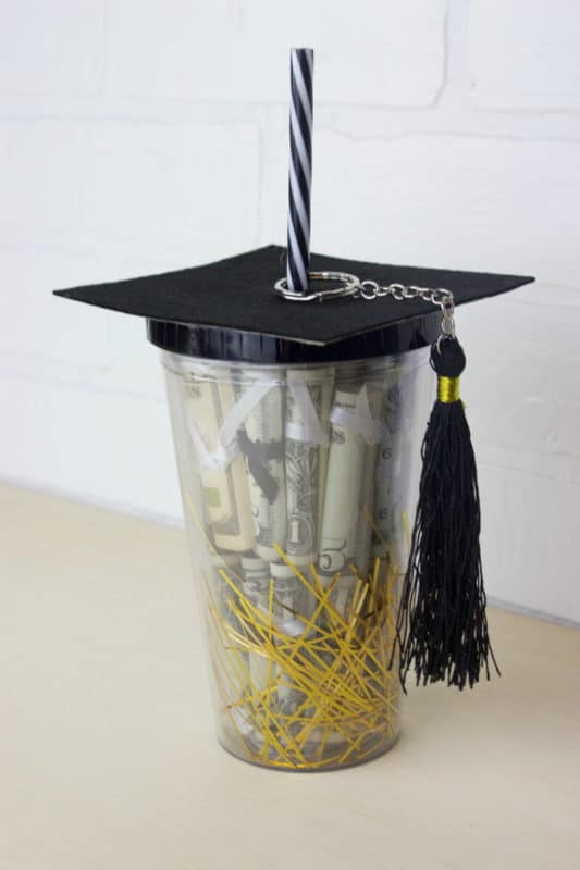 Plastic tumbler with graduation gifts inside