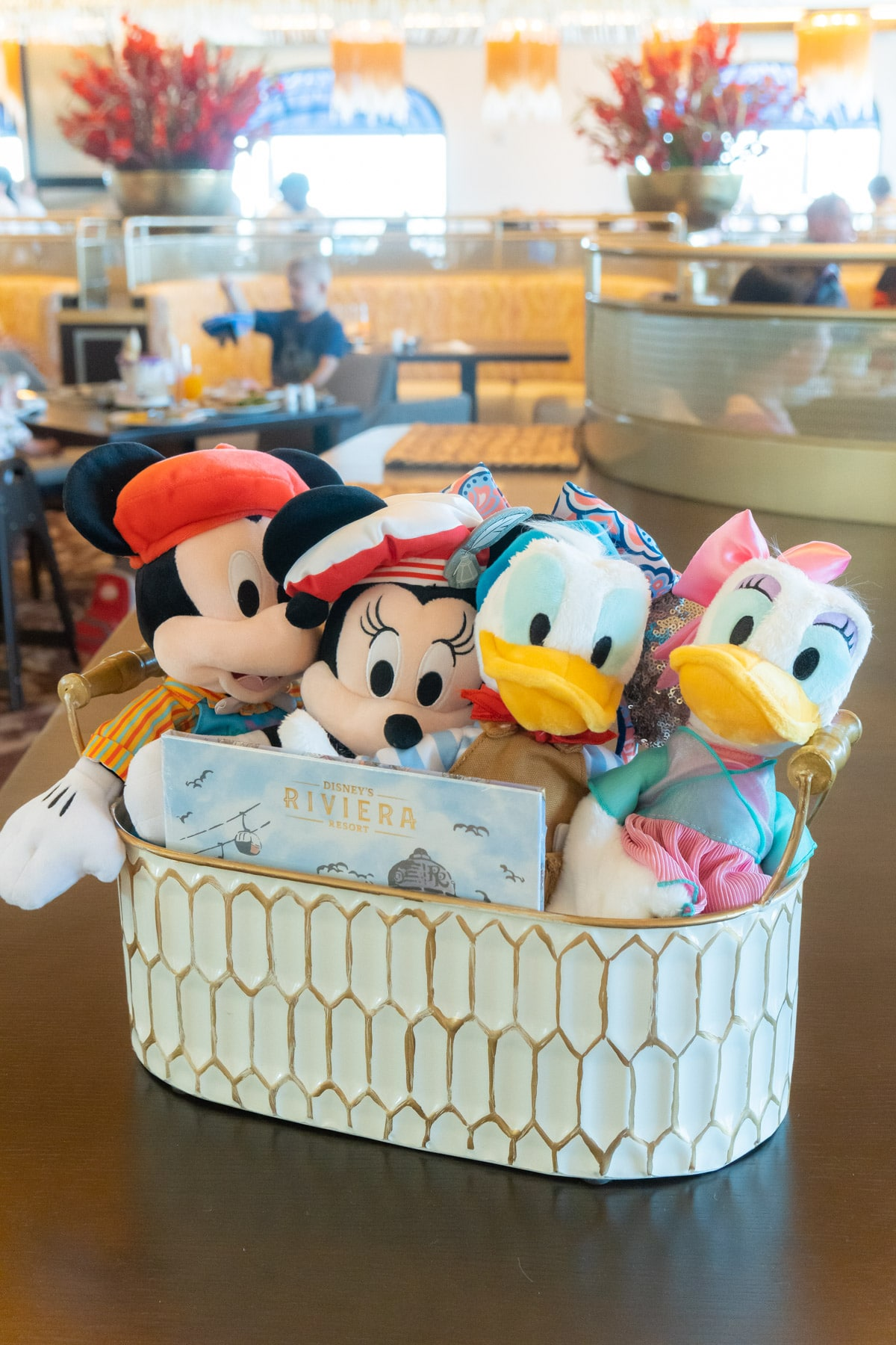Basket with plush Mickey, Minnie, Daisy, and Donald