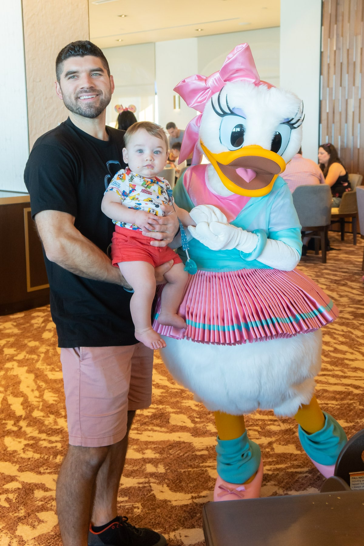 Man and baby with Daisy Duck in ballerina costume