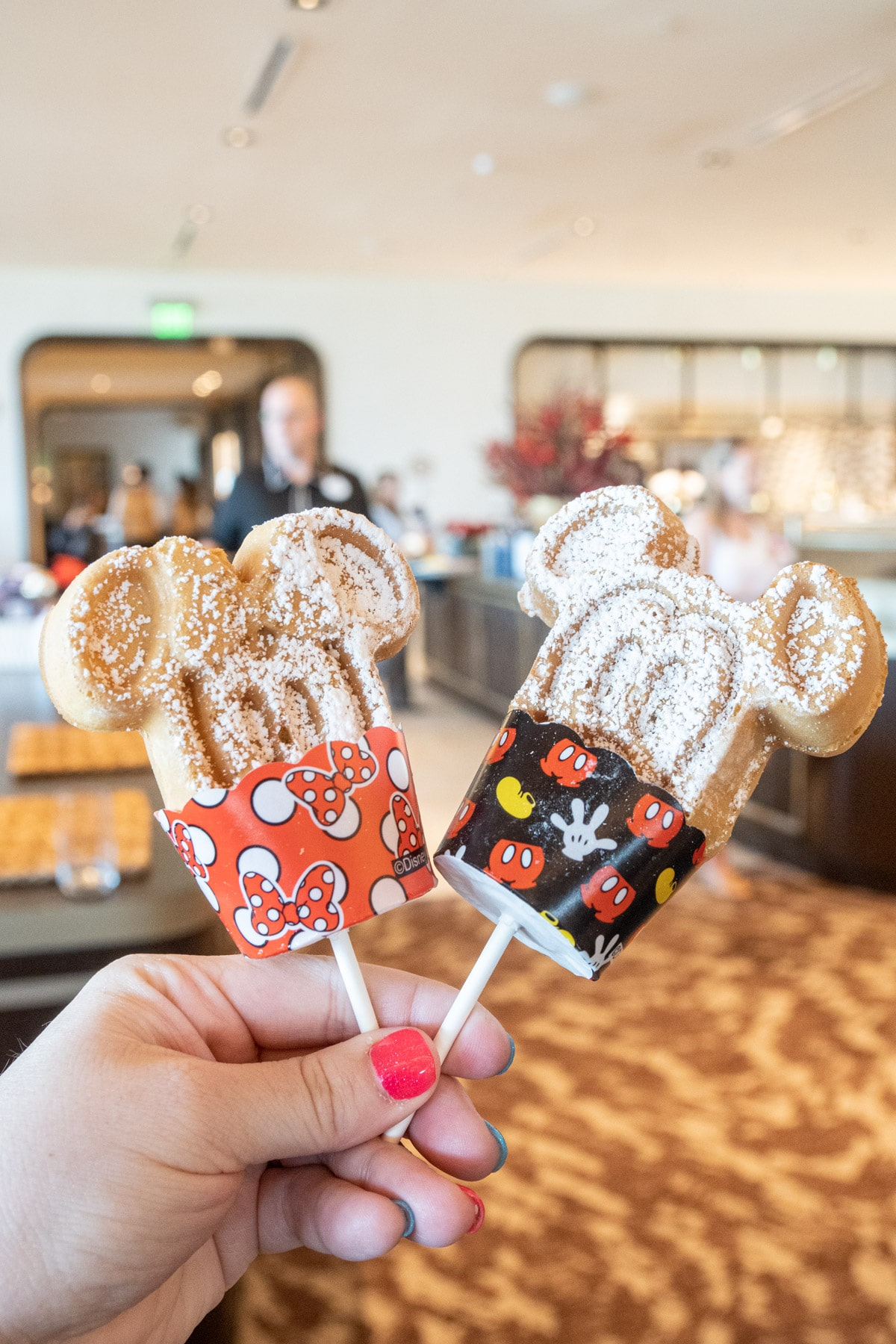 Hand holding two Mickey waffle dipper sticks