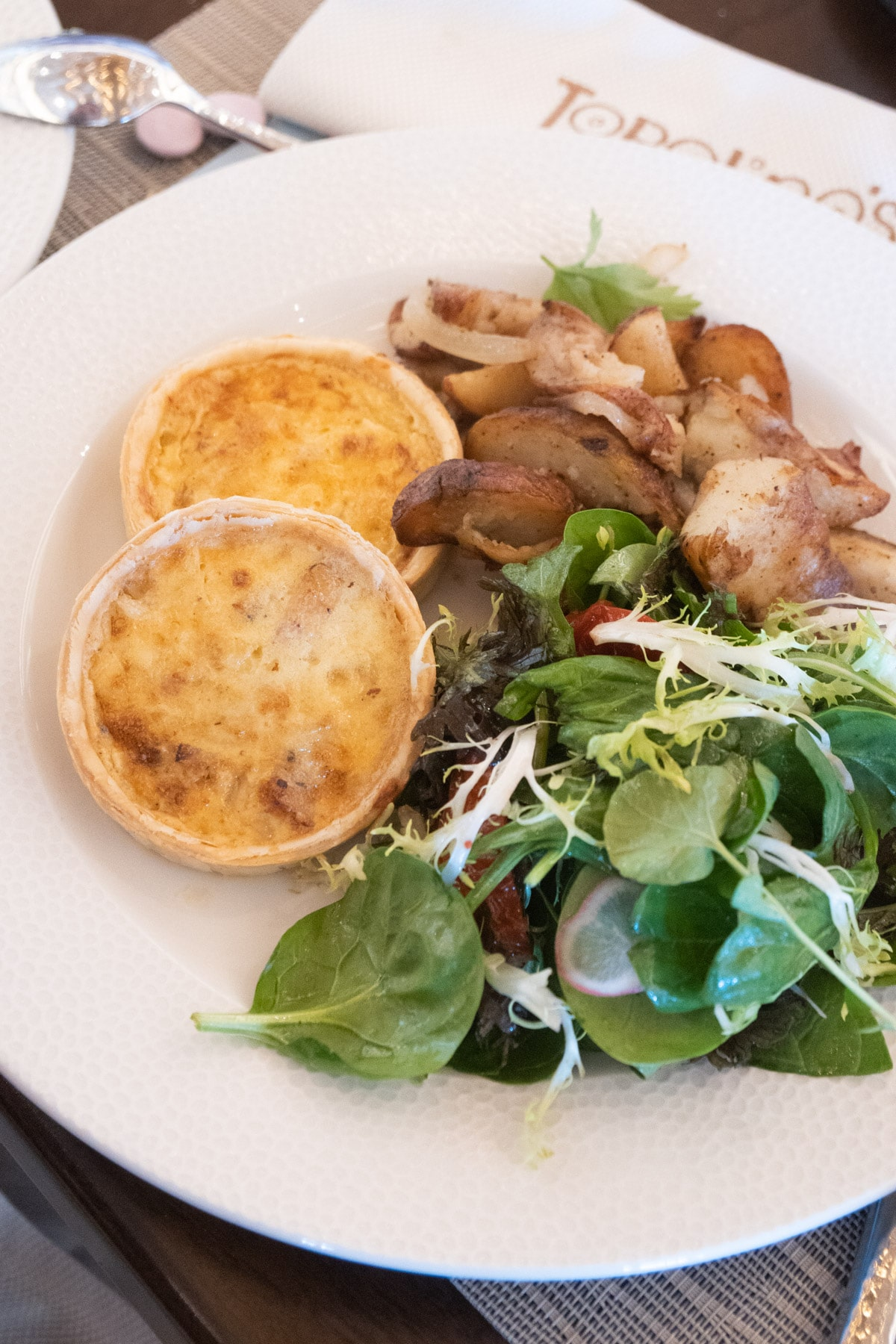 White plate with two quiche, greens, and potatoes