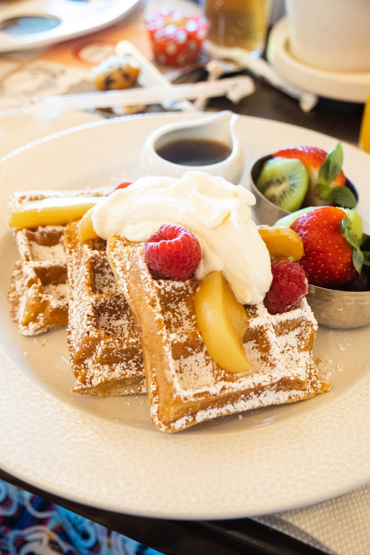 Waffle with sour cream whipped cream fruit and syrup