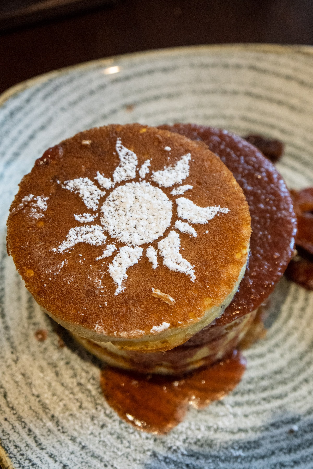 Pancakes with a Tangled symbol on top in powdered sugar