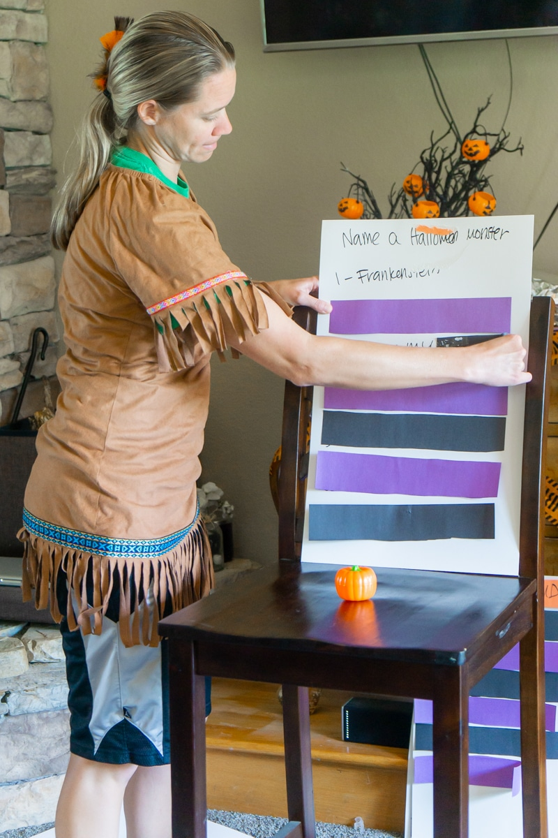 Woman removing paper from correct Halloween Family feud questions