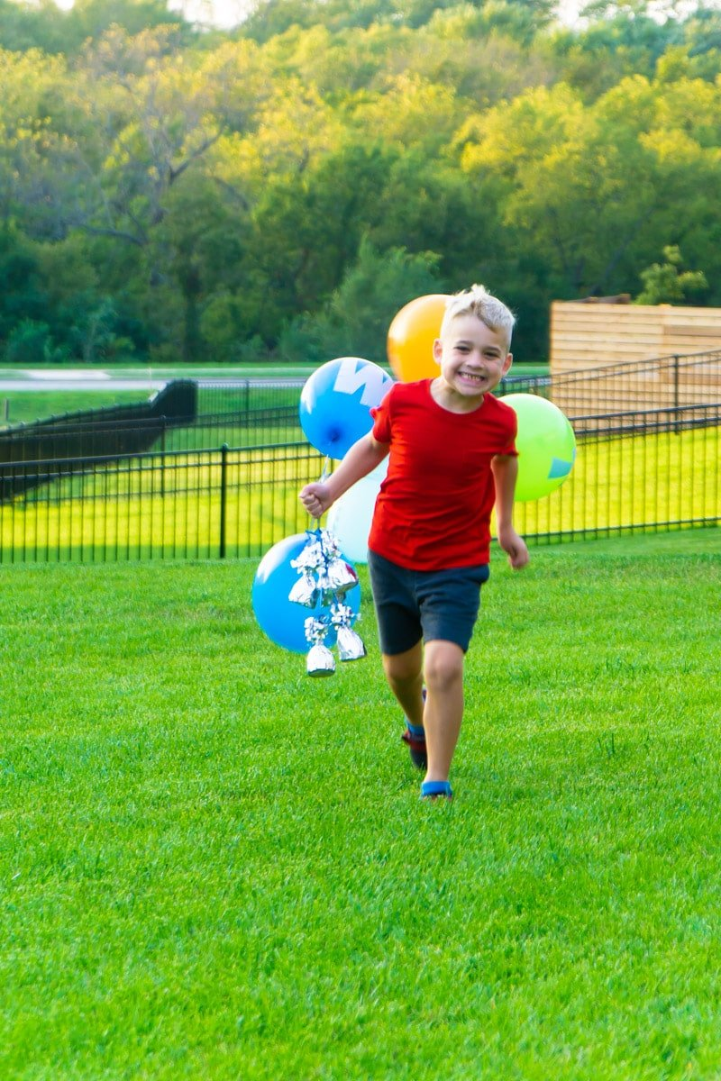 Kid holding spelling games balloons