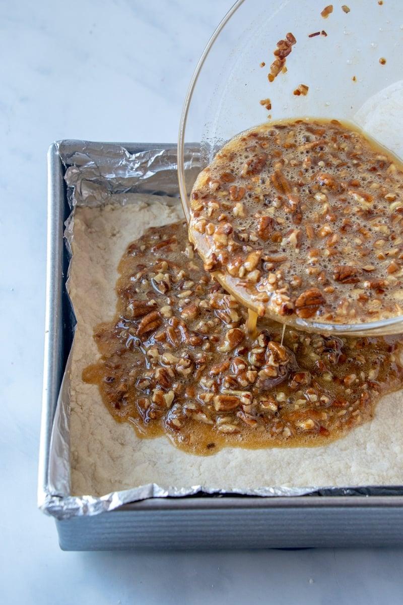 Pouring pecan pie bars onto shortbread crust