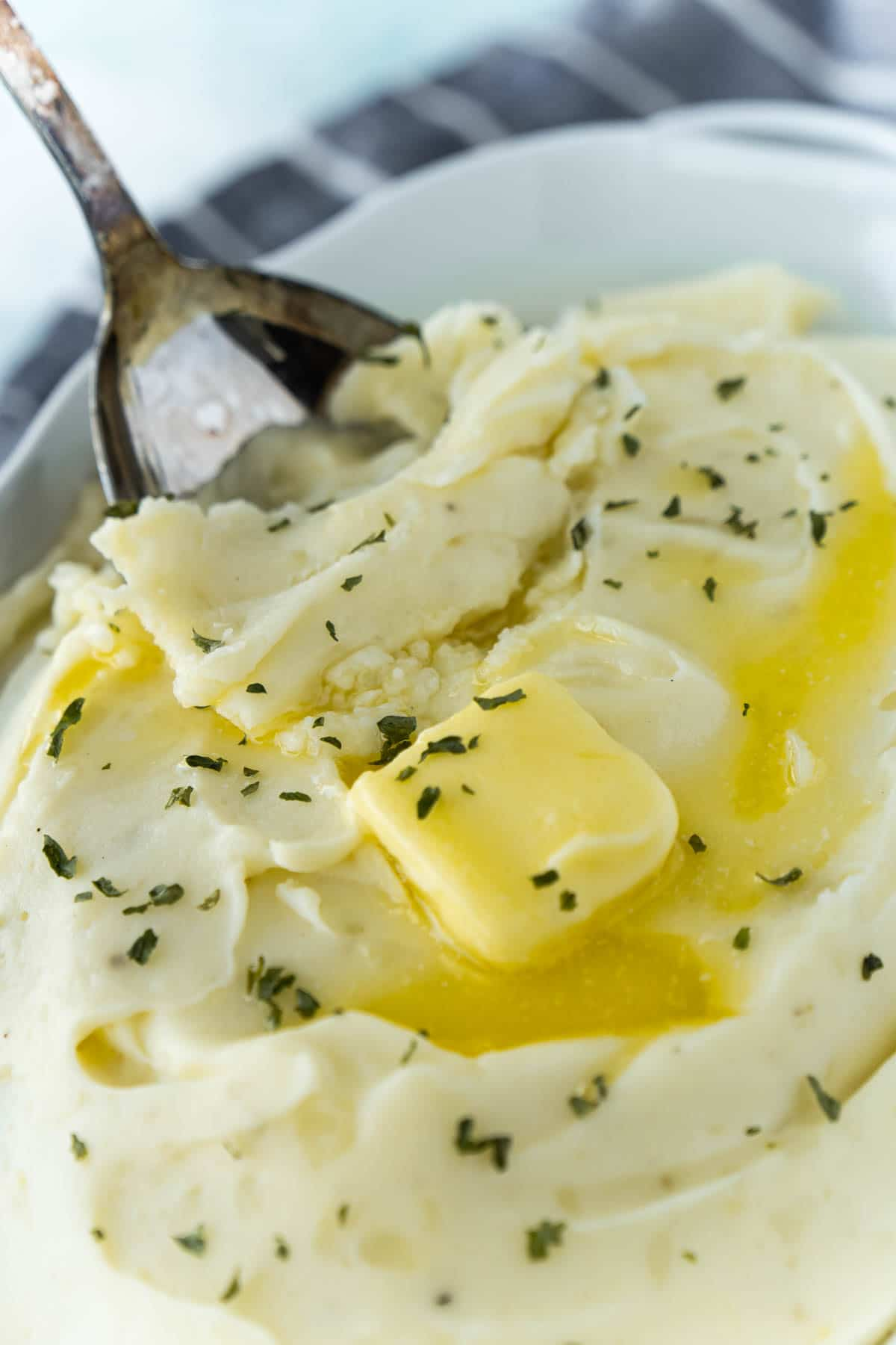 metal spoon in a bowl of mashed potatoes with butter on top