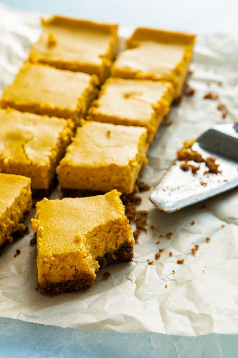 cut pumpkin cheesecake bars with a graham cracker crust