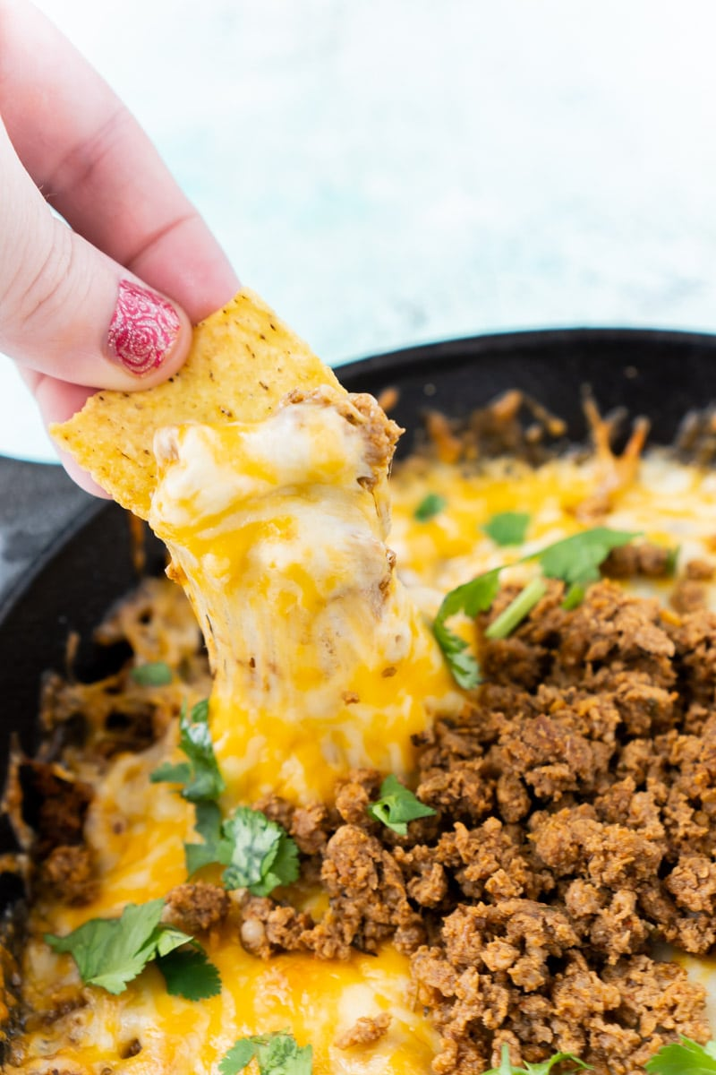 Chip dipped in queso fundido with chorizo