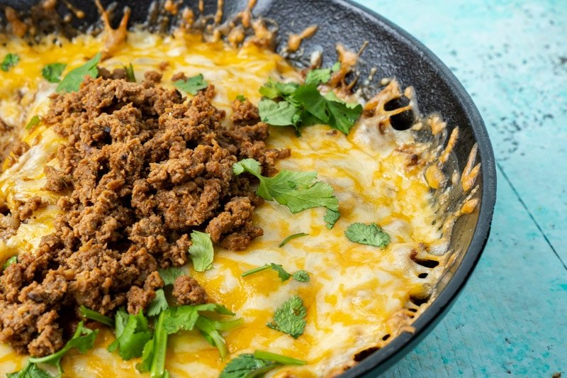 A cast iron skillet with queso fundido