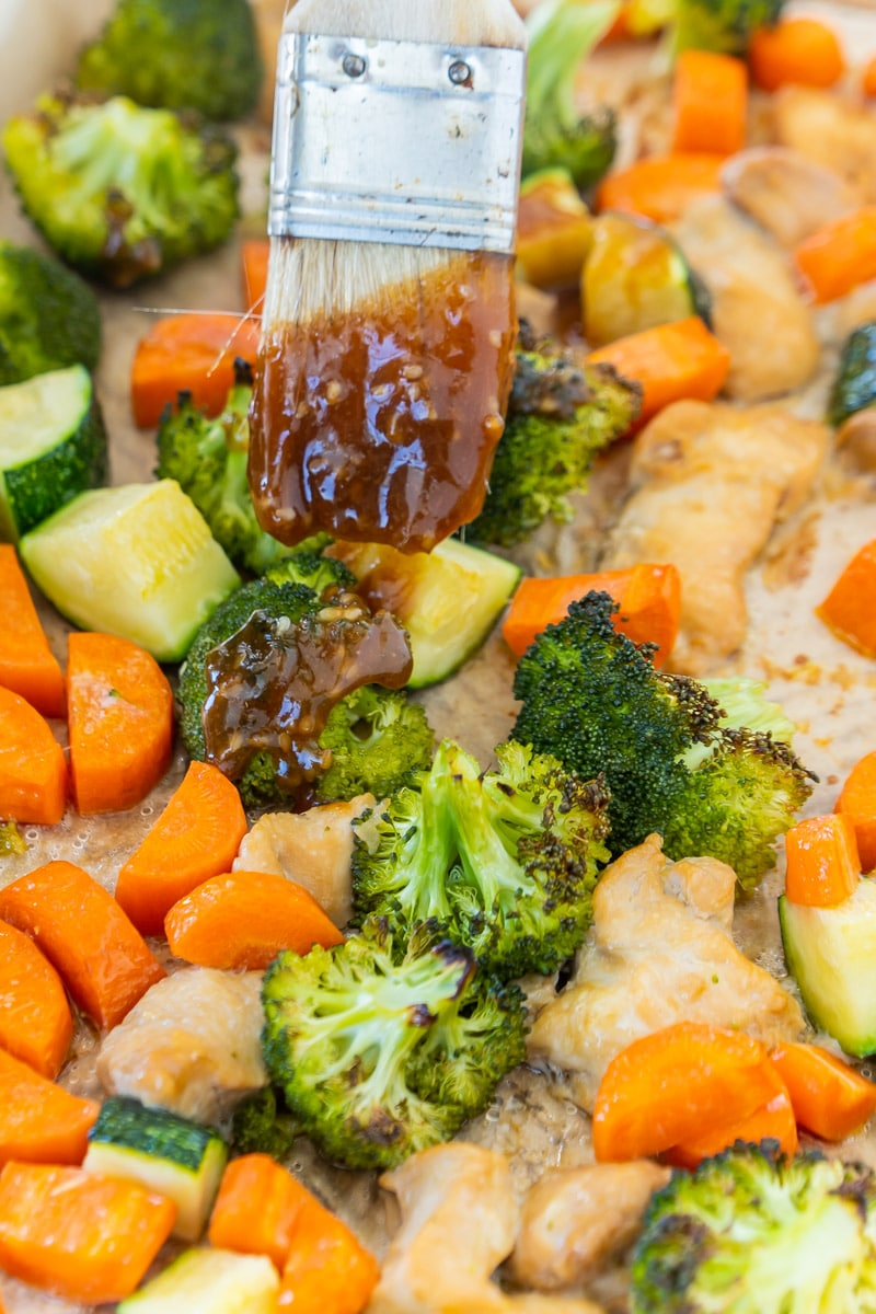 Adding teriyaki glaze to sheet pan teriyaki chicken
