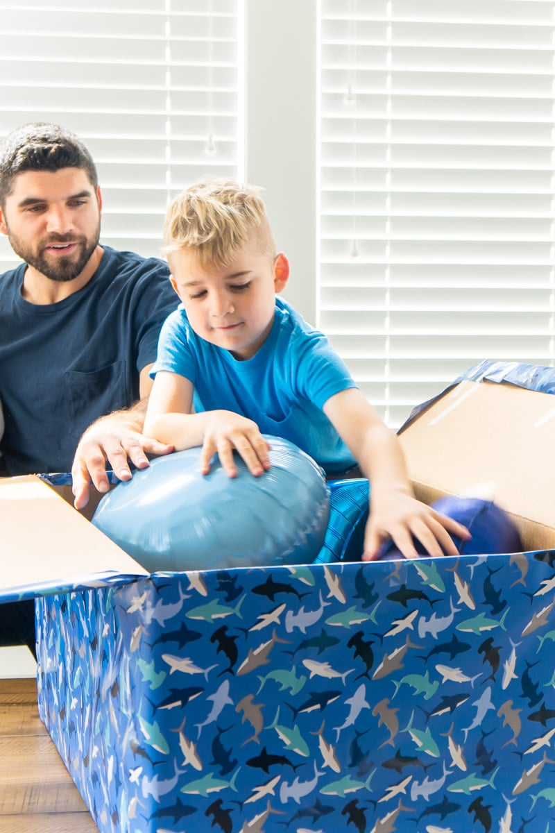 Adding balloons to blue gift box