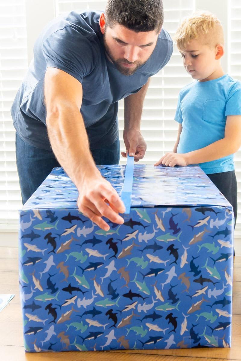 Taping blue gift box shut