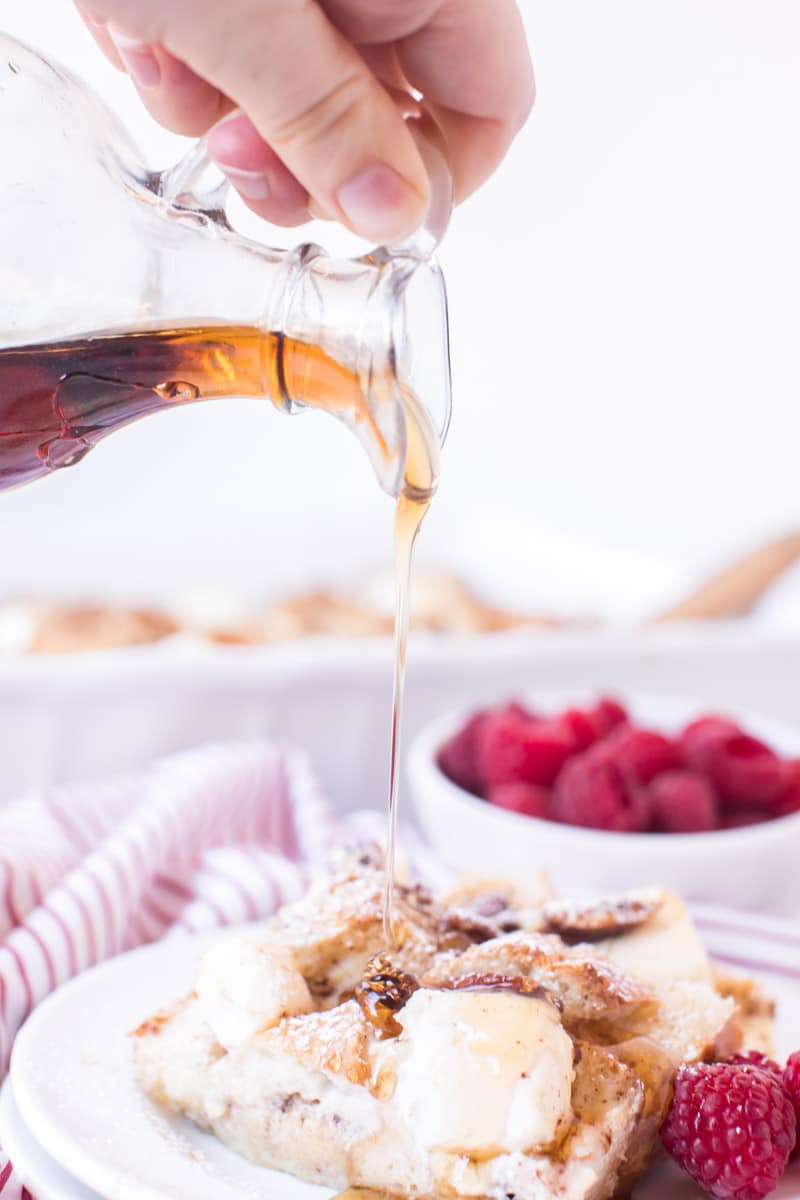 Pouring syrup on french toast casserole with cream cheese