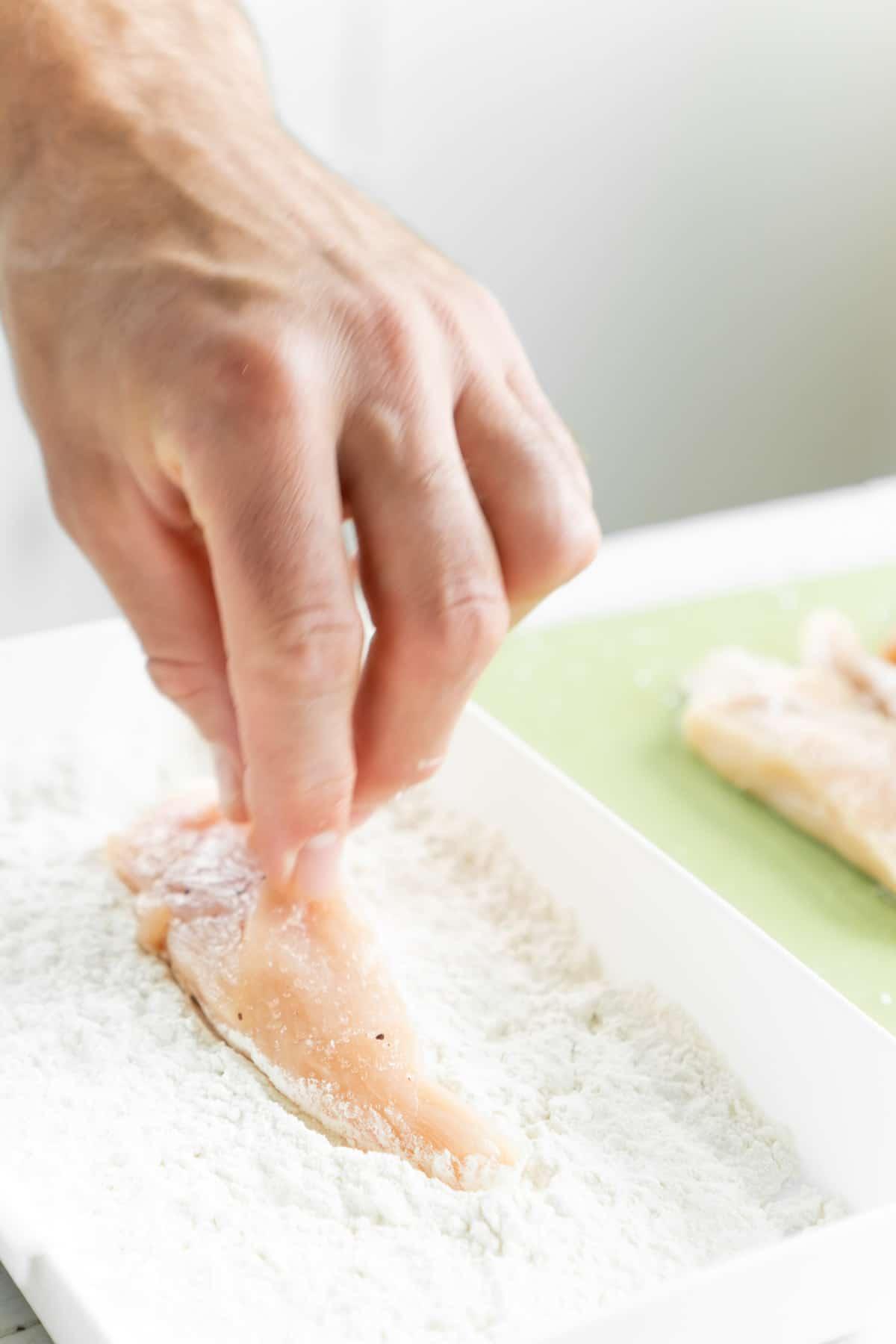 Hand putting chicken tender into dish of flour