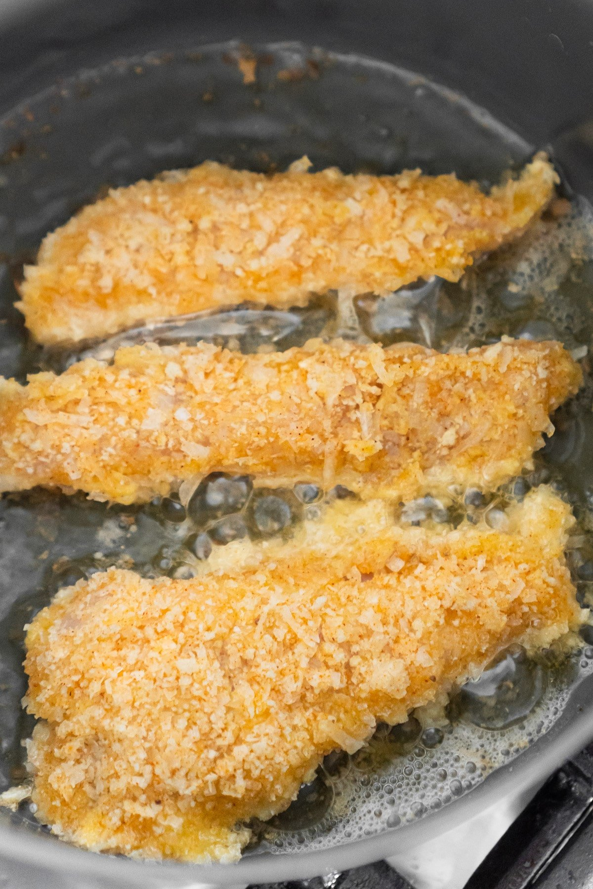 Coconut chicken tenders in coconut oil pan frying