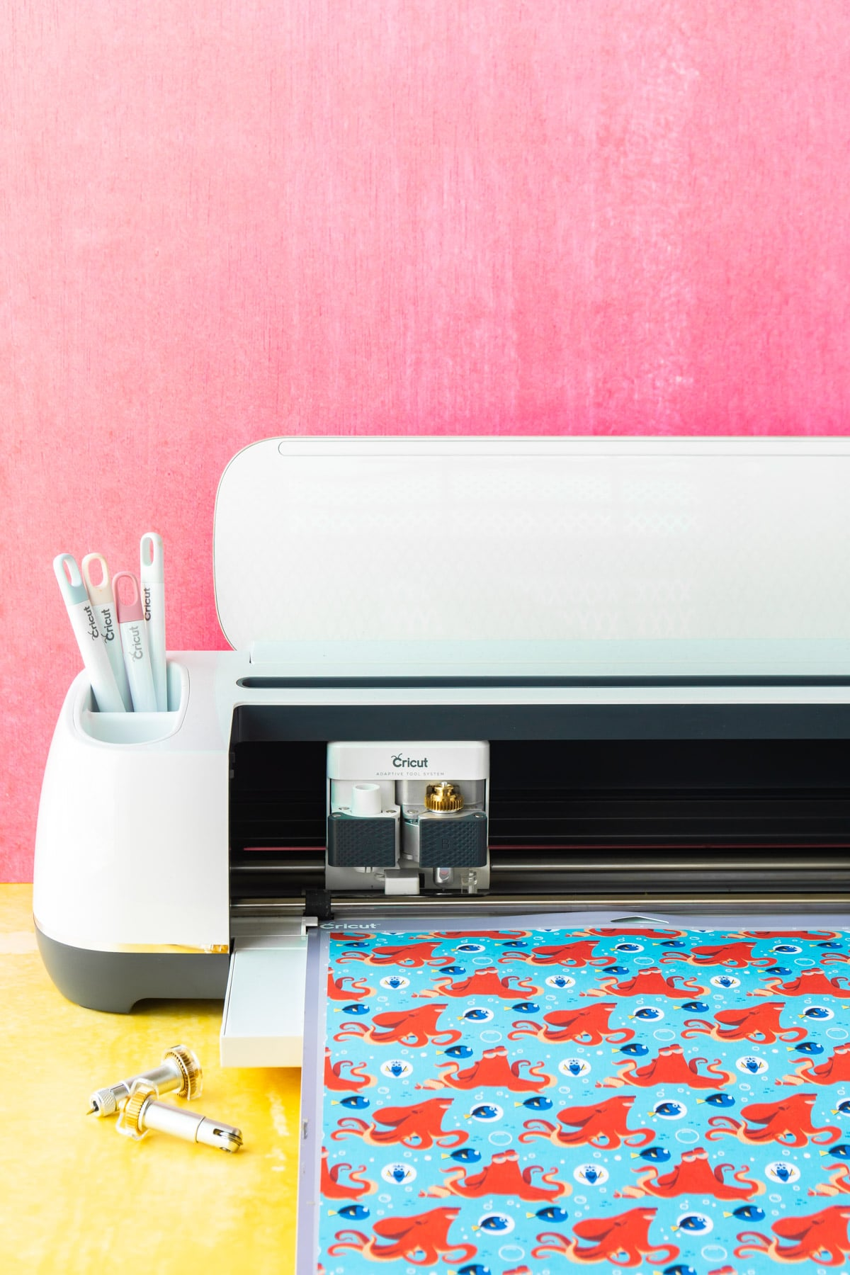 Cricut Maker on a yellow table with a pink background