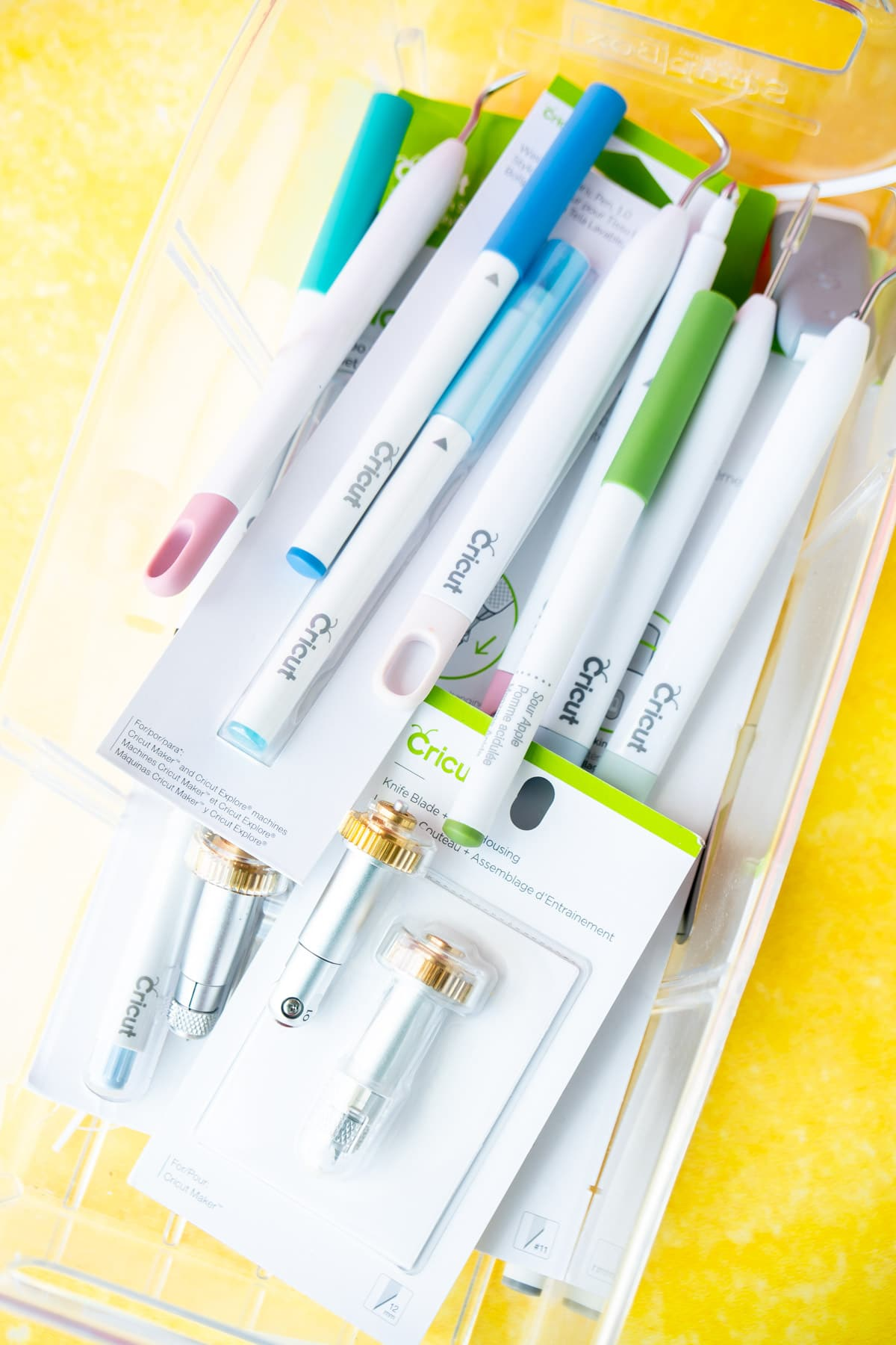 A variety of Cricut Maker tools in a clear bucket on a yellow background