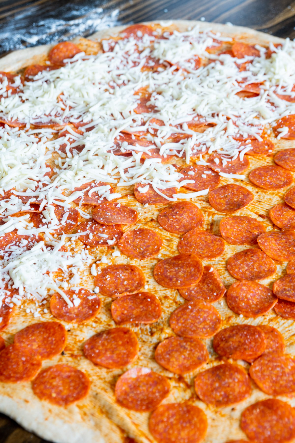 Large rolled out pizza dough covered with pepperoni and sauce