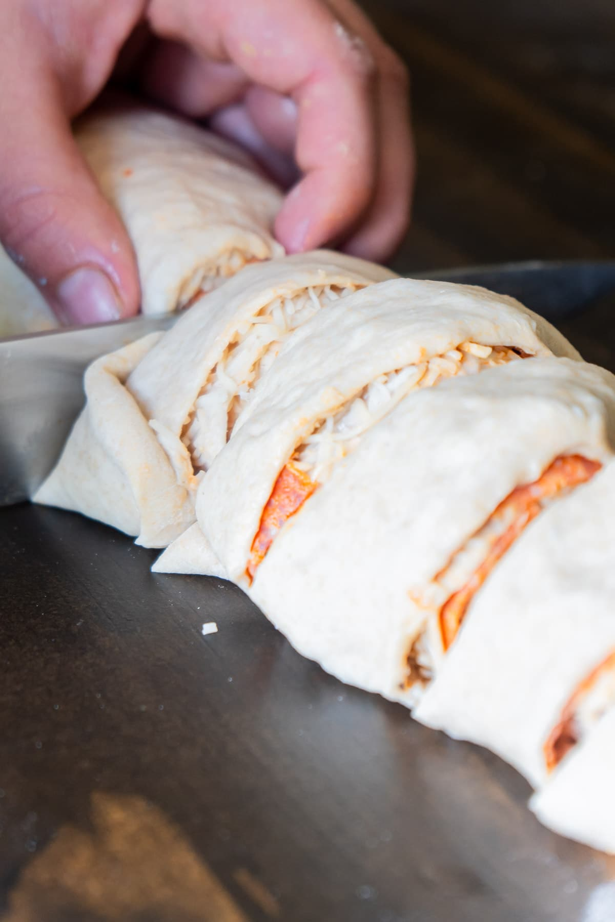 Woman cutting pepperoni rolls into pieces with large knife
