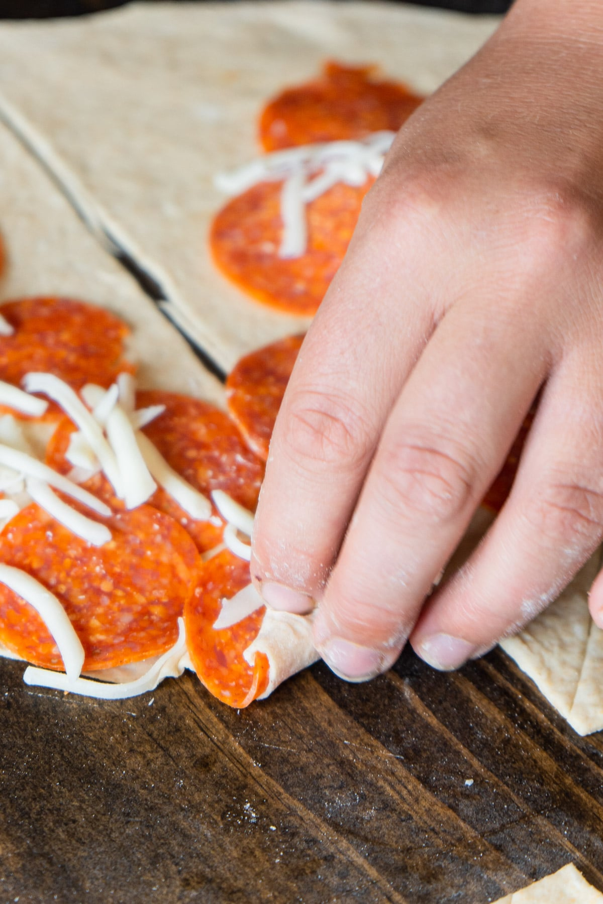Woman's hand rolling up pepperoni rolls
