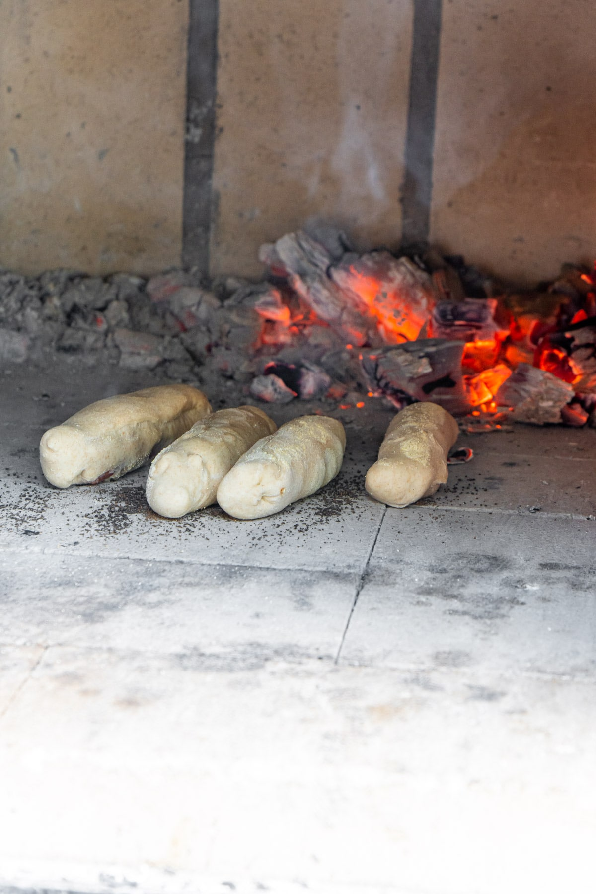 Four pepperoni rolls in a brick oven with fire in the background