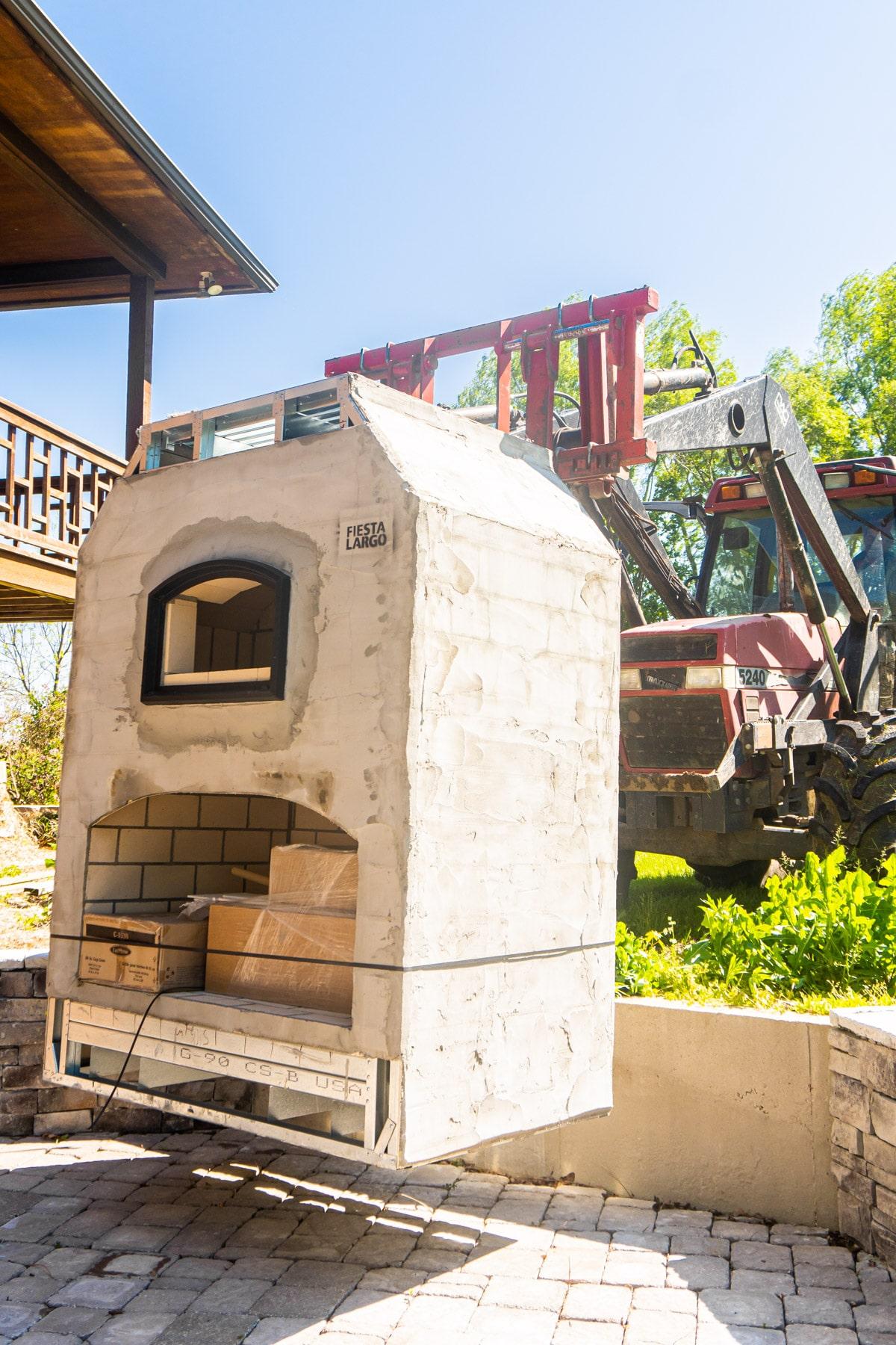 Forklift installing outdoor brick oven on backyard patio
