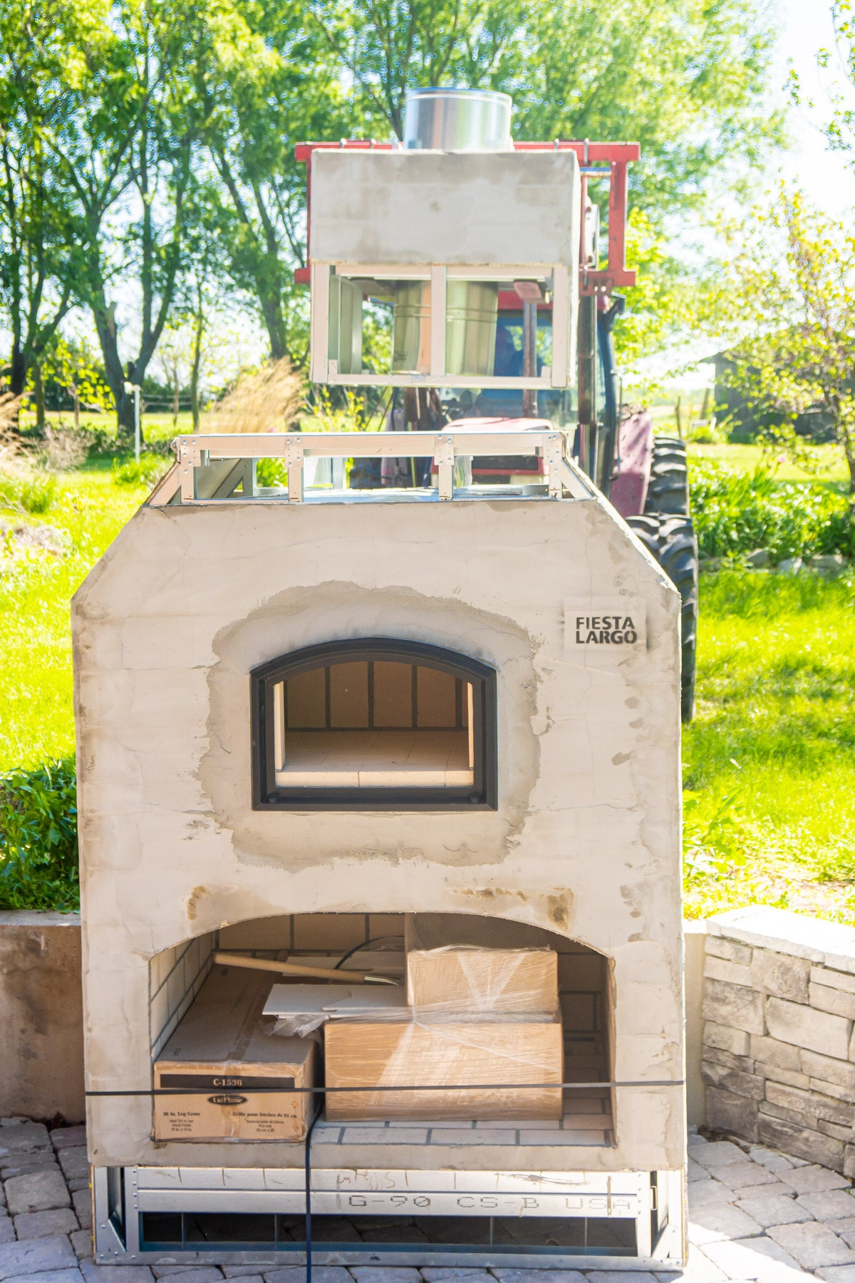 Forklift placing chimney on top of backyard brick oven