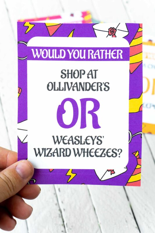 A woman's hand holding a Harry Potter would you rather card