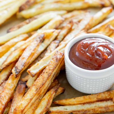 A pile of air fryer fries with a small white cup of ketchup