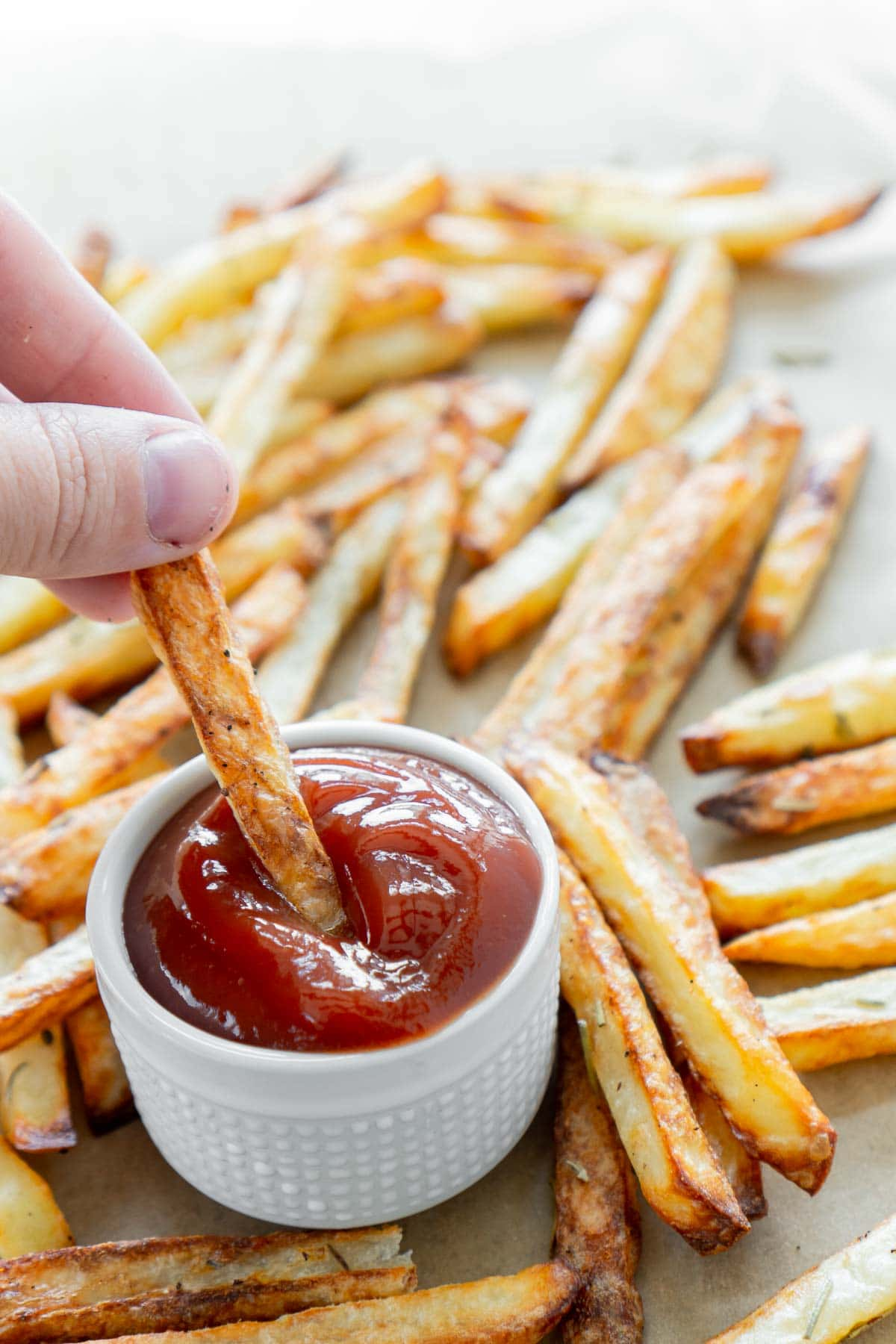 Woman's hand dipping a french fry in ketchup with a plate of air fryer fries