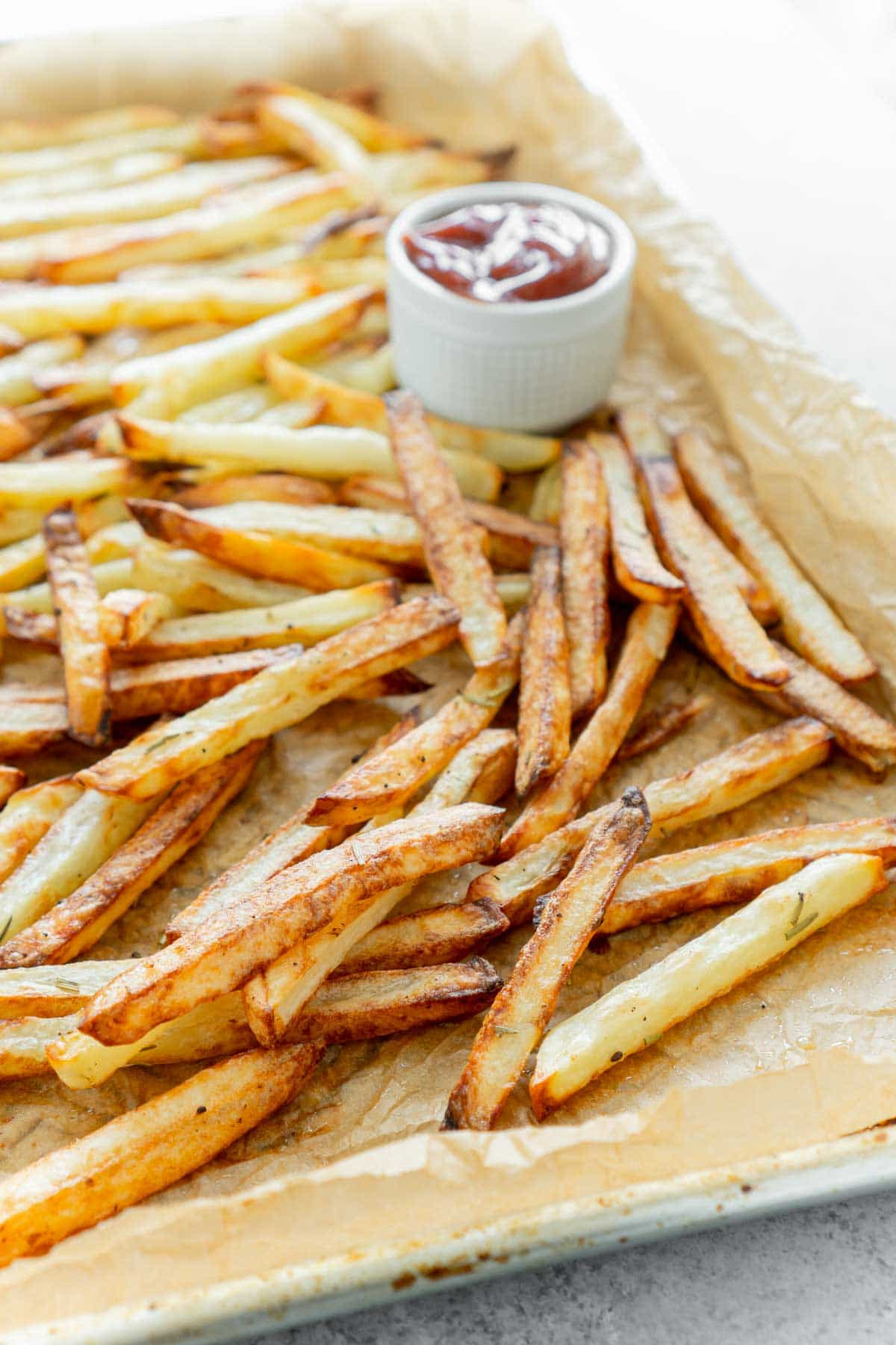 Pile of homemade fryer french fries on a baking sheet with parchment paper