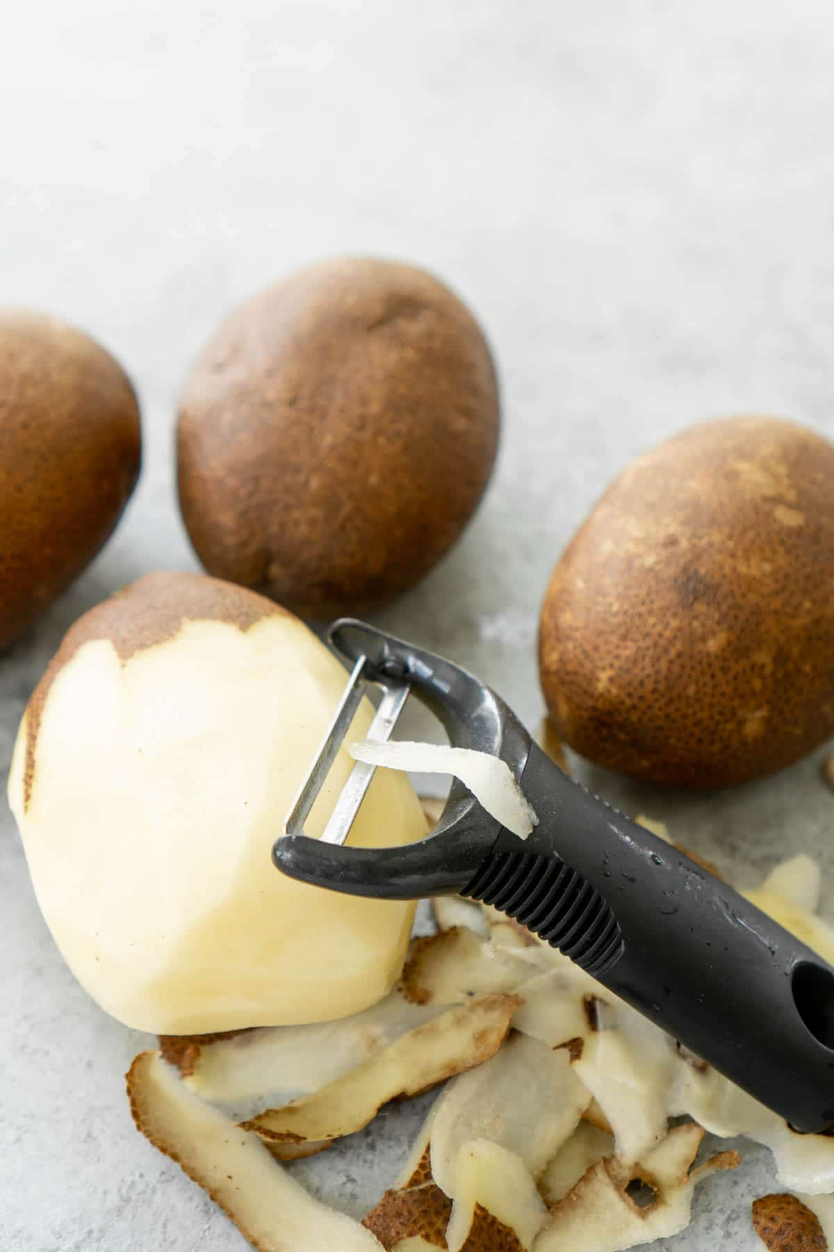 Three potatoes with a half peeled potato, potato peeler, and pile of potato peelings