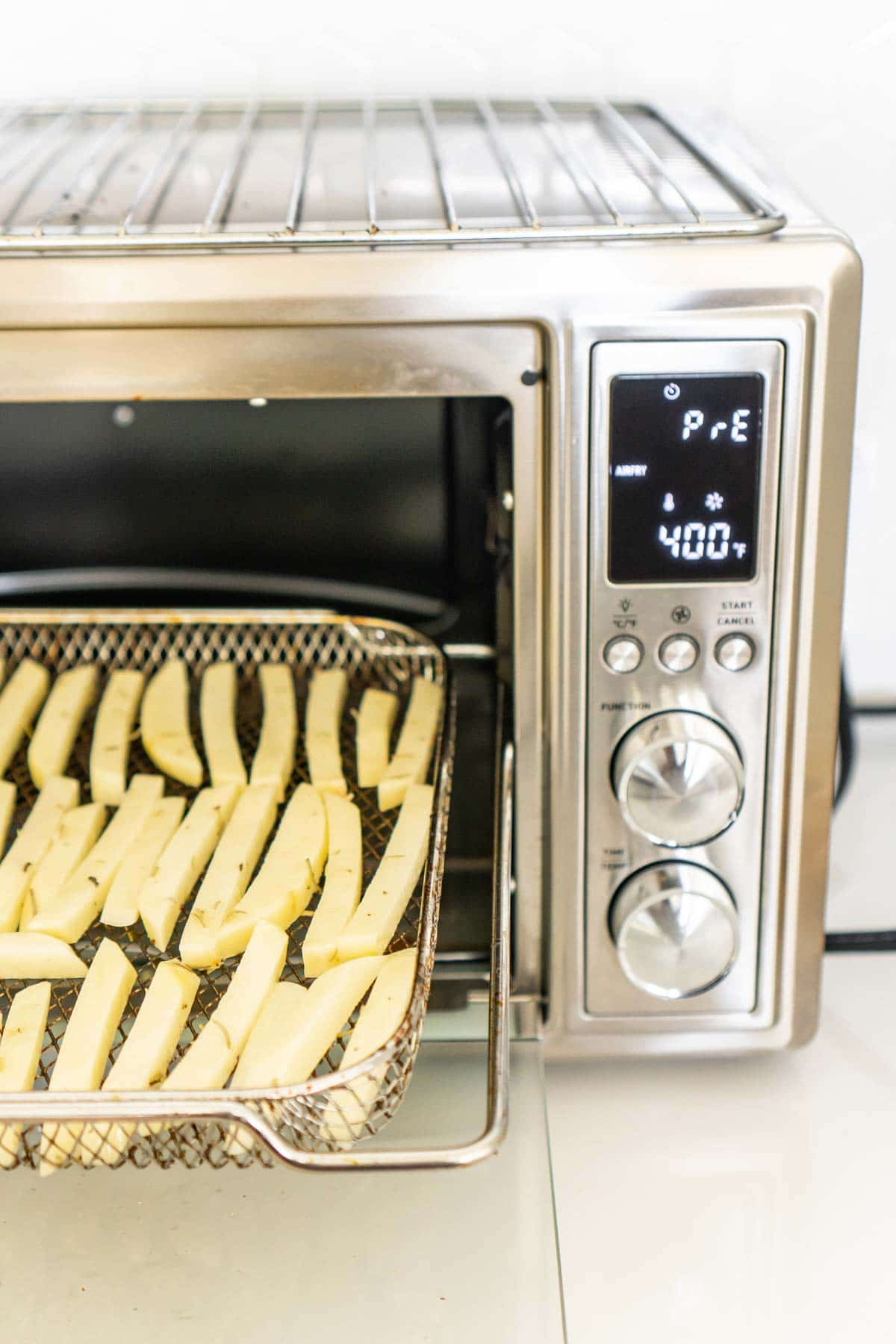 A cosori toaster oven air fryer with a rack full of cut potatoes