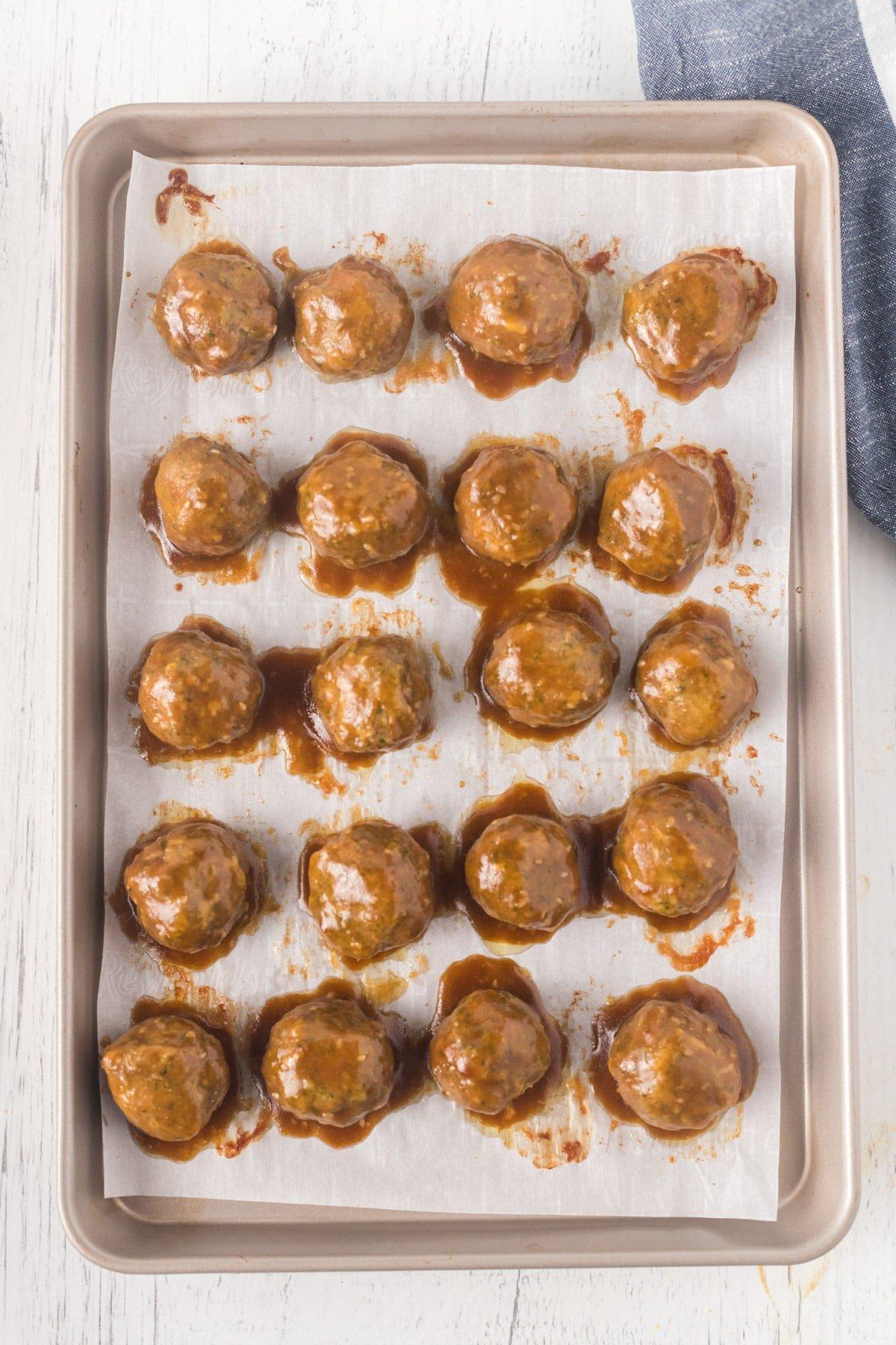 Baked turkey meatballs covered in teriyaki sauce on a baking sheet