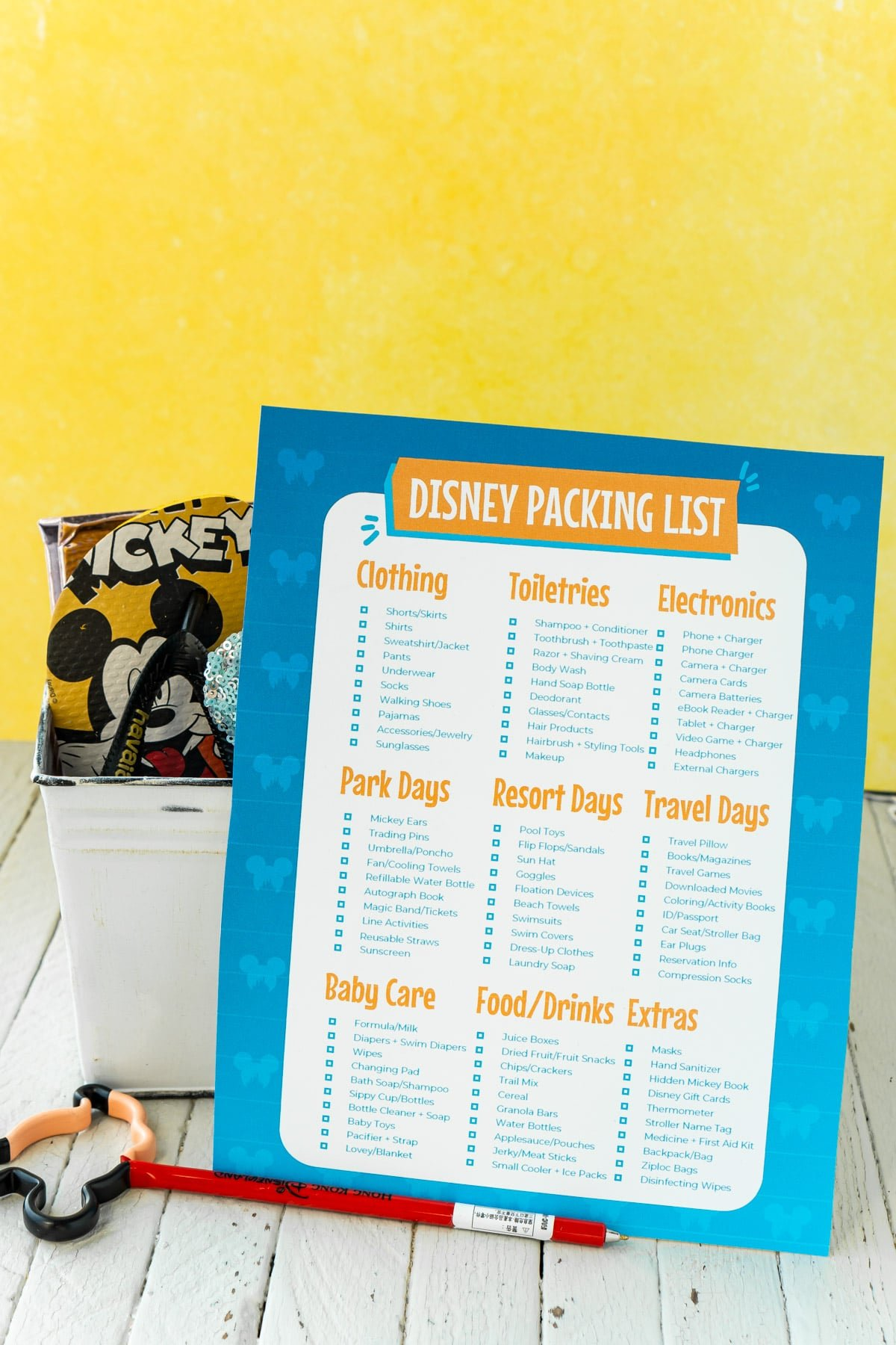 Disney packing list in front of a bucket full of Disney items with a yellow background