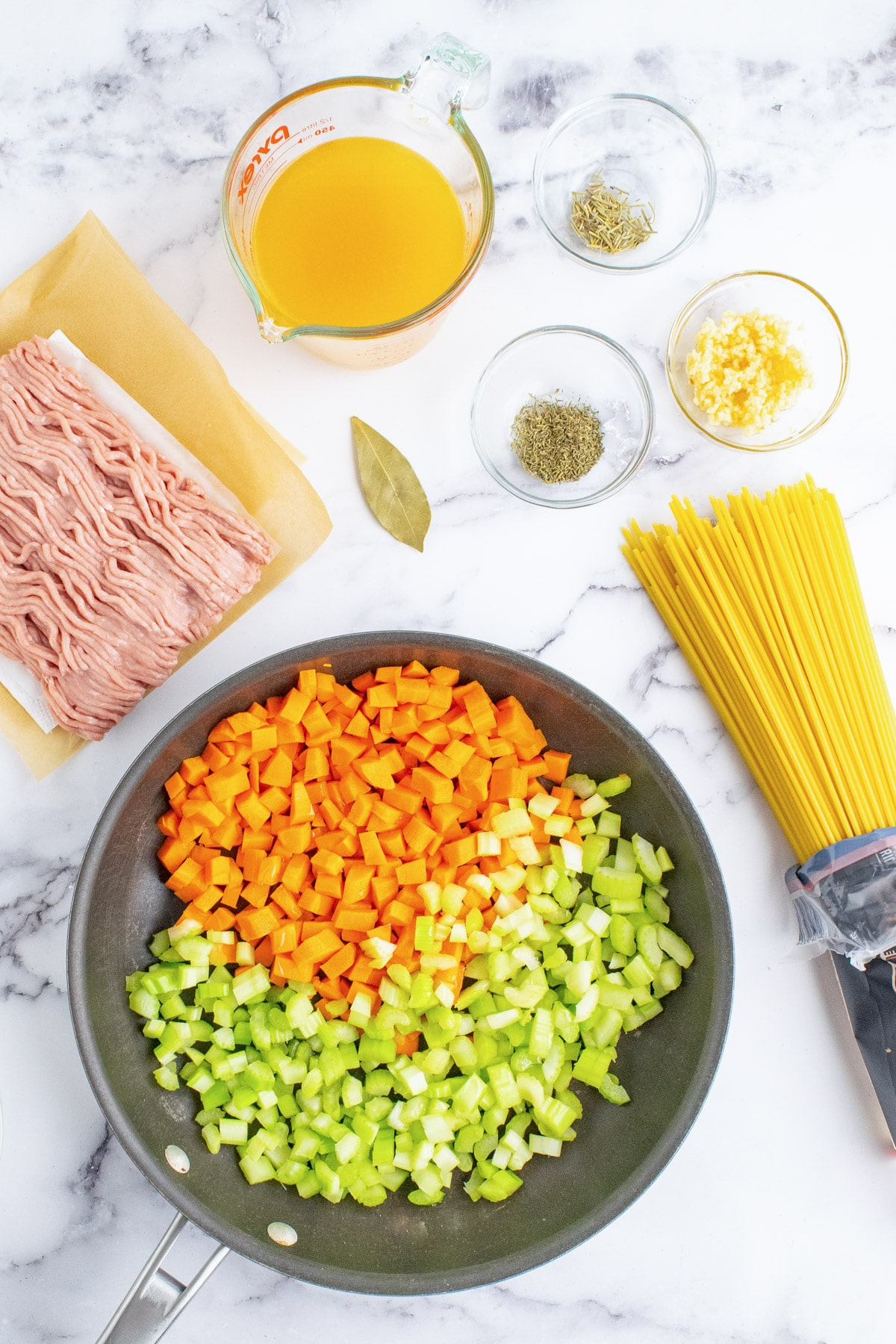 Celery and carrots in a pan with other ingredients for ground turkey pasta around it