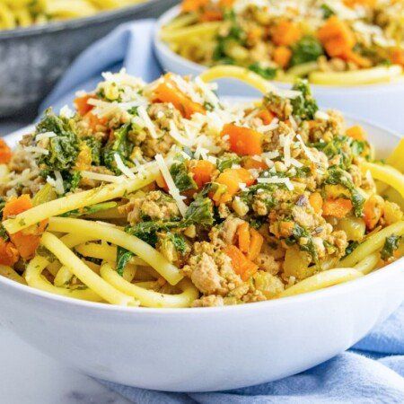 A horizontal bowl of ground turkey pasta with kale and carrots