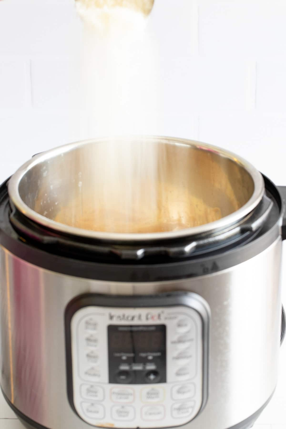 A hand putting cheese into an Instant Pot