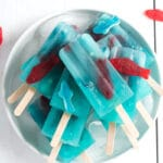 A pile of blue lemonade popsicles with Swedish fish inside on a bowl of ice