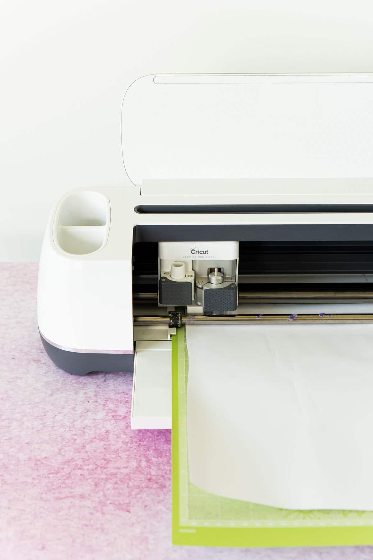 Cricut Maker with a piece of white vinyl on a green mat