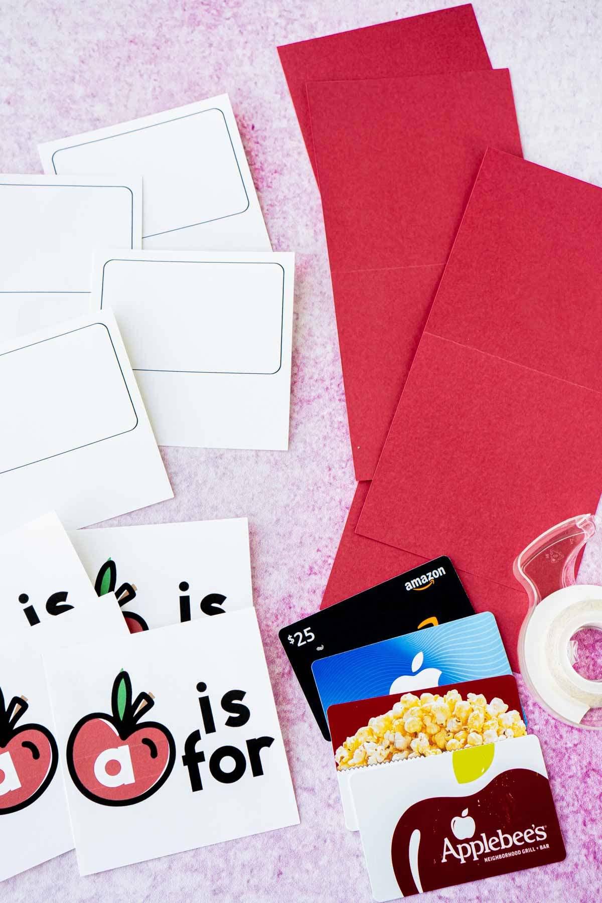 Apple cards, gift cards, and red cardstock in a flat lay
