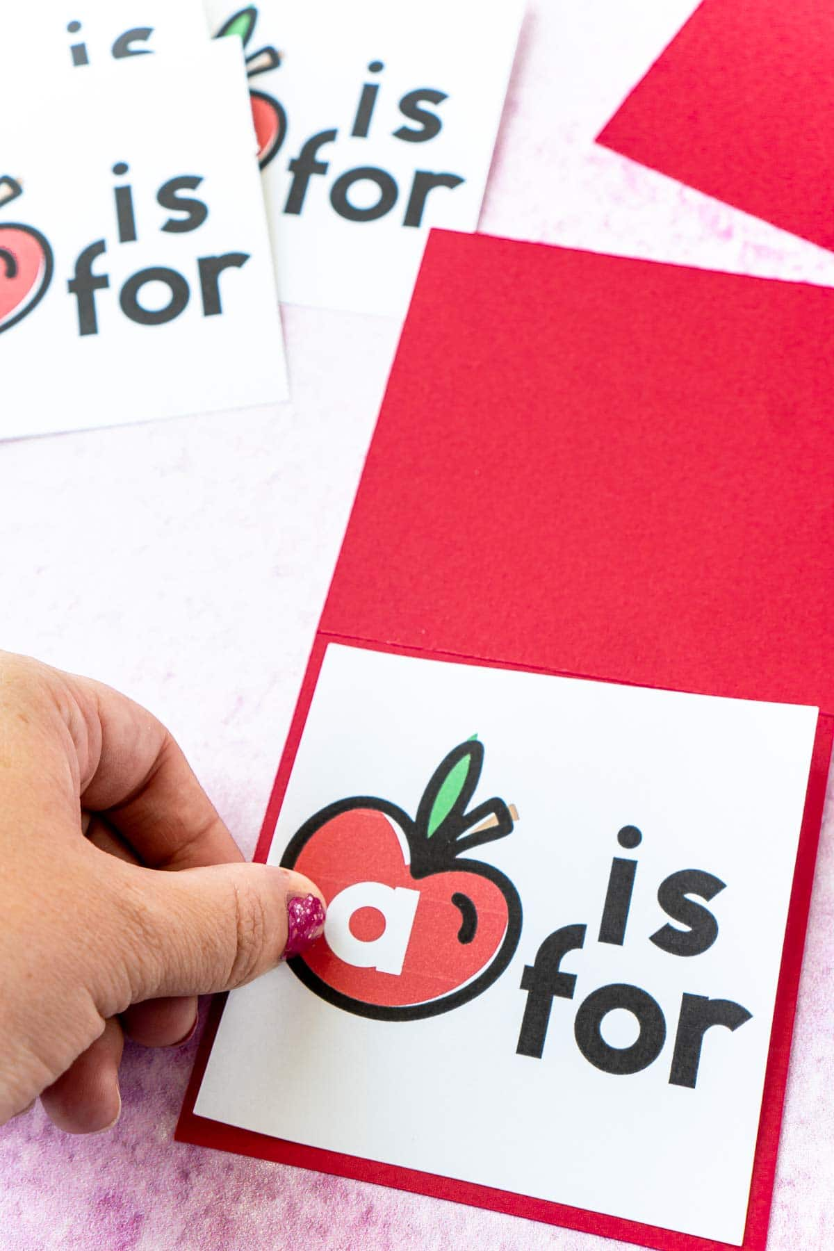 Woman's hand adding an apple card to a piece of red cardstock