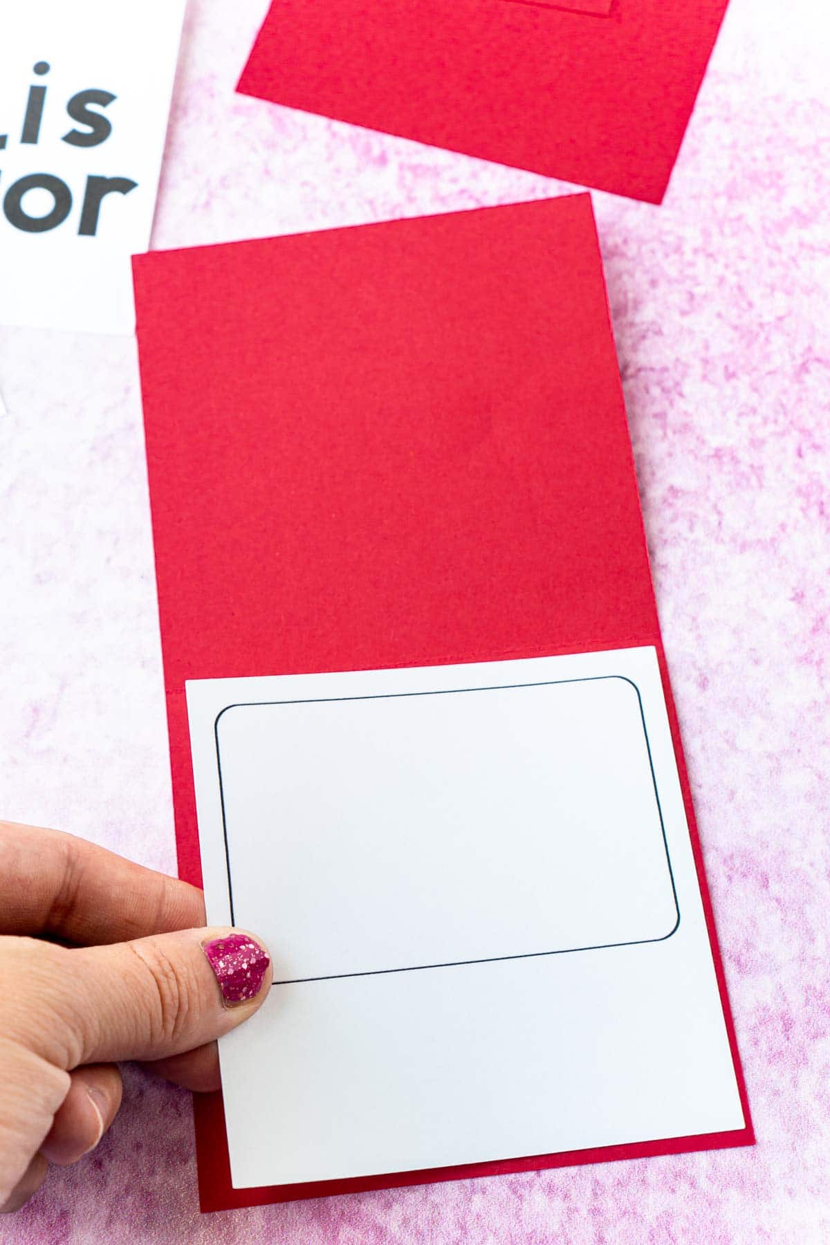 Woman's hand adding a gift card holder to a red card