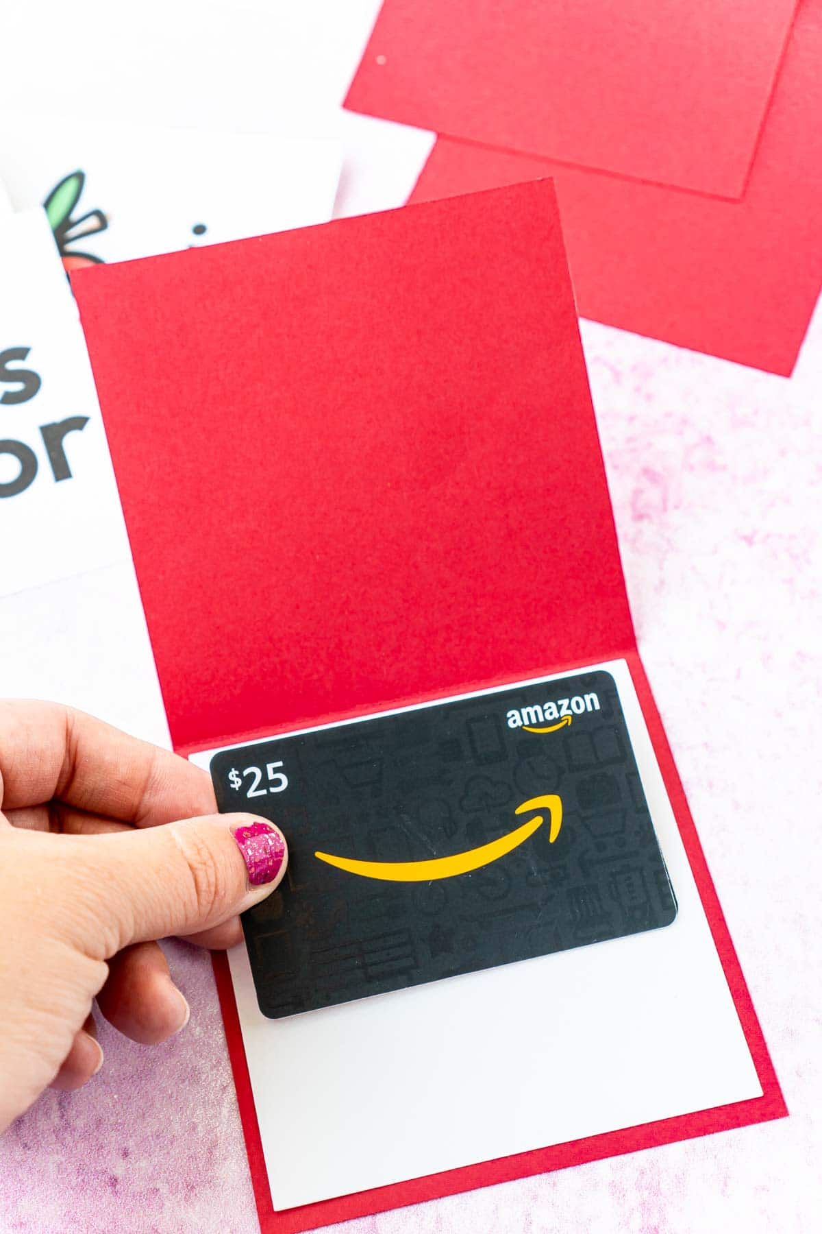 Woman's hand adding a gift card to a red card