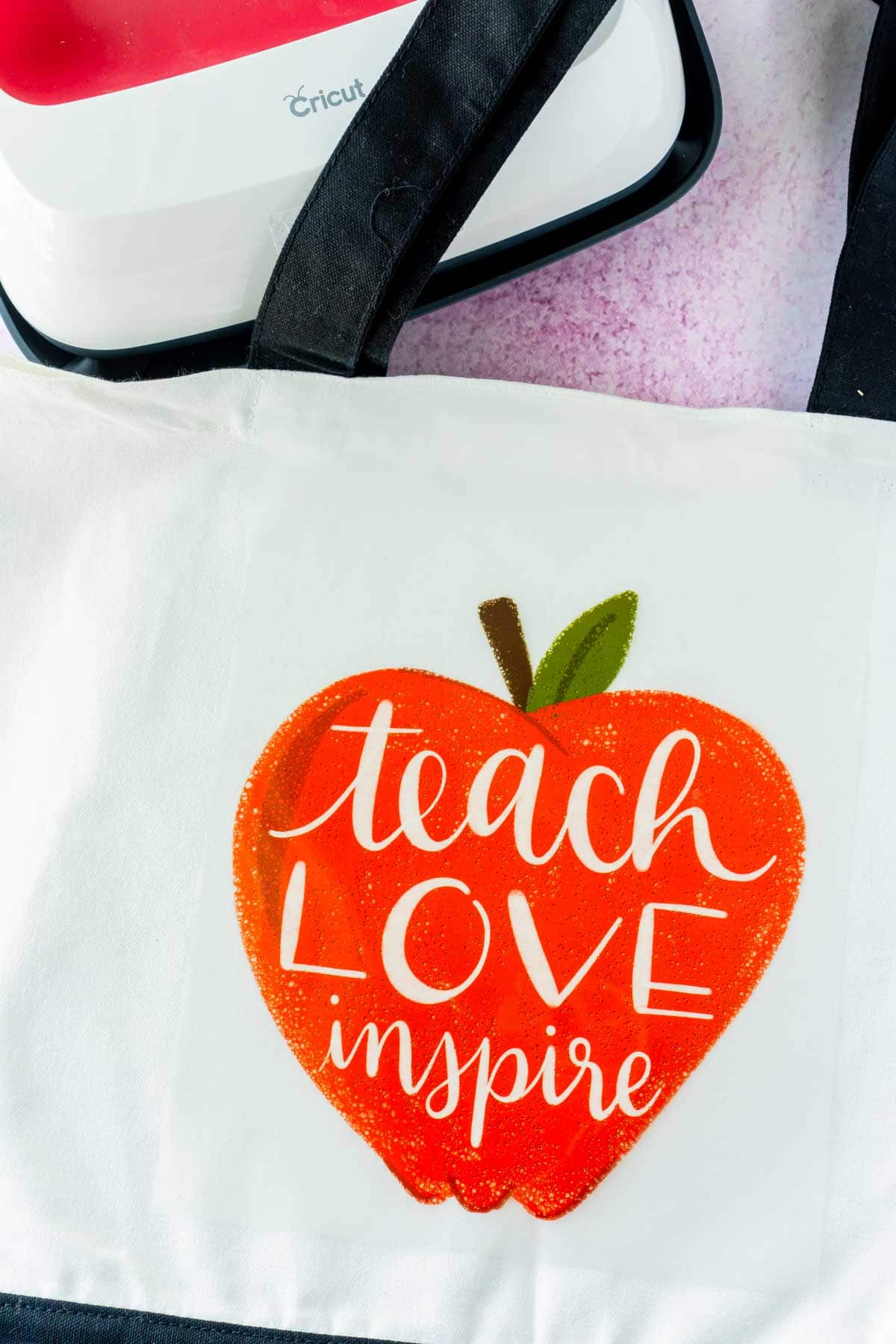 Apple iron-on design on top of a white tote bag